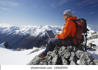 Side view of a male mountain climber using laptop on mountain peak