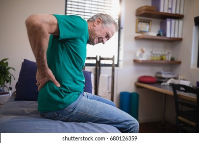 Side view of male patient grimacing from back ache while sitting on bed at hospital ward