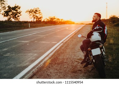 Side view of male in protective equipment sitting sideways on motorcycle laying hand on helmet on roadside at sunset on backlit background of empty highway