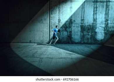 Side view of male runner who runs under arcades which are lighted with spotlights