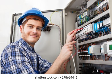 Side view of male technician examining fusebox with multimeter probe