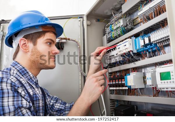 Seitenansicht des männlichen Technikers, der den Fusebox mit Multimeter-Sonde untersucht