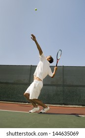 Side view of a male tennis player serving ball on court