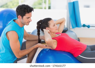 Side view of a male trainer helping woman with her exercises at a bright gym