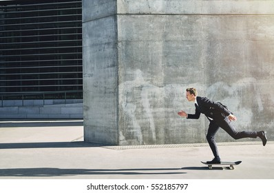 Side view of a man in black suit on a skateboard going fast