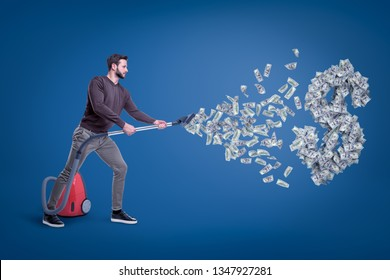 Side view of man in casual clothes hoovering up dollars and big dollar sign with vacuum cleaner. Wasting money. Doing financial damage. Acting carelessly.