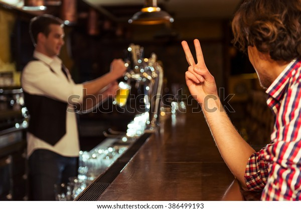 Side view of man in casual clothes ordering beer while sitting at bar counter in pub, a bartender in the background