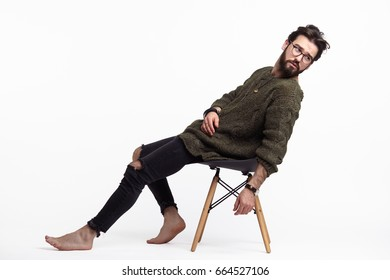 Side view of man in casual clothing sitting barefoot on chair in studio.
