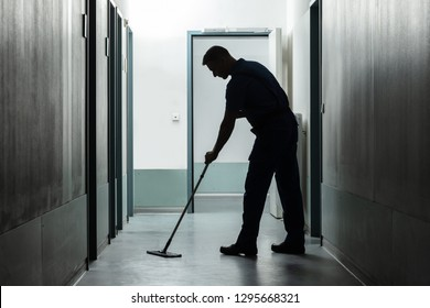 Side View Of Man Cleaning Floor With Mop
