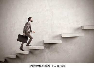 Side view of a man climbing the stairs built in a blank concrete wall. Concept of success and achieving your goal. Mock up