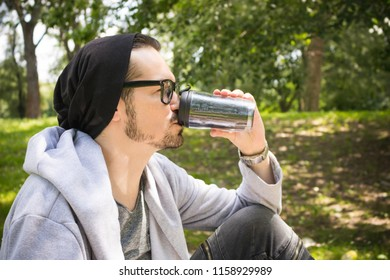 Side view of man drinking coffee from reusable cup while spending day in nature.