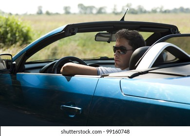 Side view of a man driving his convertible car
