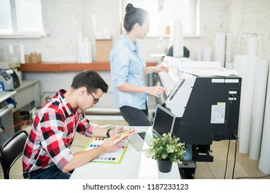 Side view of man exploring palette of colors and woman working with printing machine in modern office