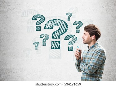 Side view of a man holding a marker and standing near a concrete wall with blue question mark sketches on it. Concept of problem solving