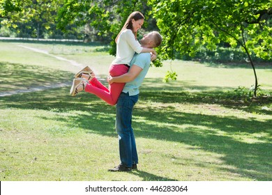 Side View Of Man Lifting Woman At Park