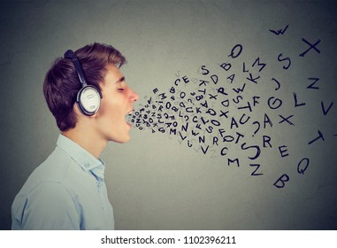 Side view of man listening to music in earphones and singing with letters coming out of mouth on gray
