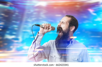 Side view of a man with a long beard singing in a microphone standing against a blurred blue background. Mock up toned image