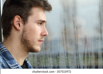 Side view of a man longing and looking through window in a sad rainy day