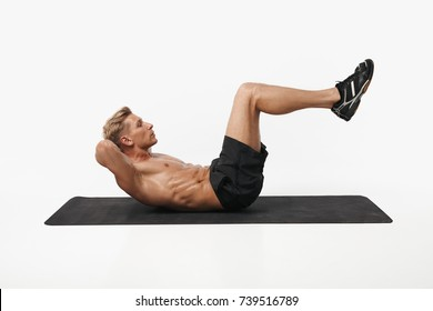 Side view of man lying on mat and doing knee crunches on white studio background.