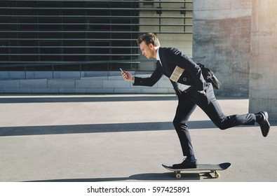 Side view of a man on a skateboard movingwith determination looking at his phone