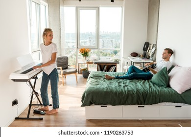 side view of man playing acoustic guitar on bed while girlfriend playing electronic piano at home