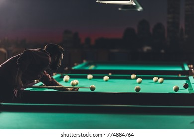 side view of man playing in russian pool at bar