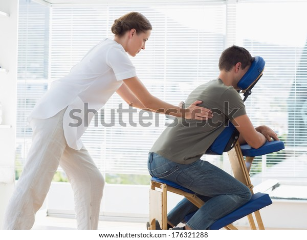 Side view of man receiving back massage from physiotherapist in hospital
