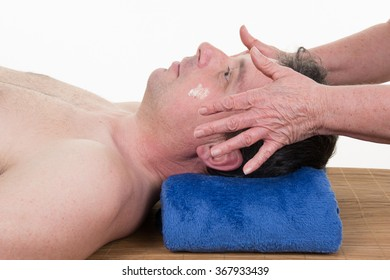 Side view of a man receiving a head massage at health spa