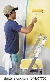 Side view of a man with roller applying yellow paint on a wall