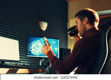Side view man sitting in a leather chair working in the studio using a smartphone and computers. Freelancer holds mobile phone working on footage, video, design.