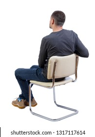 Side view of a man sitting on a chair. Rear view people collection.  backside view of person.  Isolated over white background. Stylish guy in boots sits on a white chair.