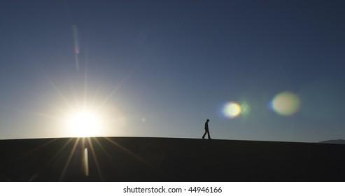 Side view of man walking in desert with sun at horizon. Horizontal shot.
