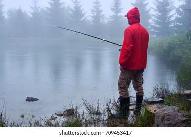 Side view of man in waterproof jacket fishing on Lake Synevyr