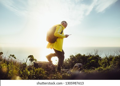 Side view of a man wearing backpack walking on a rocky hill. Senior man hiking on a hill looking at his mobile phone with sun in the background.