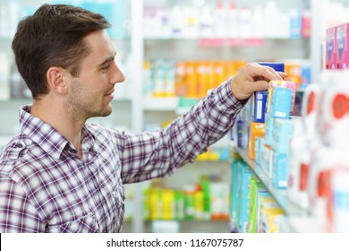 Side view of man wearing in checked shirt choosing medicines in drugstore. Male customer standing, looking at shelf with medical products and taking medicament in hand.