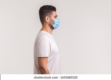 Side view of man wearing hygienic mask to prevent infection, respiratory illnesses such as flu, 2019-nCoV. indoor shot isolated, copy space for advertise about coronavirus, Covid-19prevention awarenes