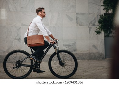 Side view of a man wearing an office bag riding a bike. Businessman going to office on a bicycle listening to music.