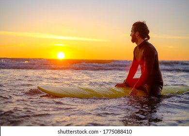 Side view of man in wetsuit sitting on surfboard and resting in sea while surfing with friend during sunset
