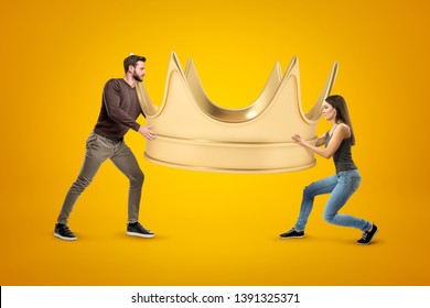 Side view of man and woman, both in casual clothes, carrying enormous gold crown on yellow background. Who runs house Who is boss in family Authority and power.