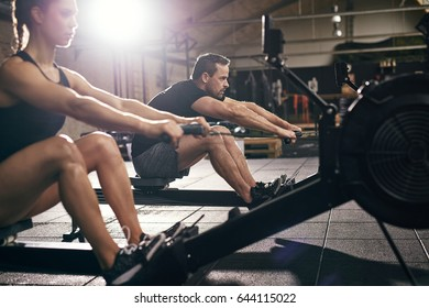 Side view of man and woman doing exercises with rowing machine at gym.