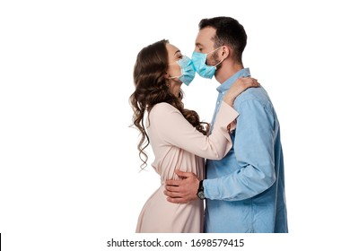 side view of man and woman in medical masks kissing isolated on white