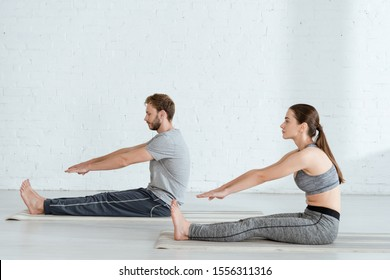 side view of man and woman practicing yoga in seated forward bend pose