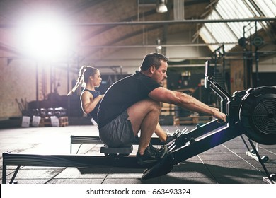 Side view of man and woman in sportswear working out on rowing machines in light gym.