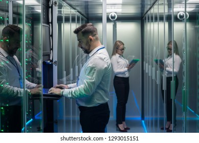 Side view of man and woman with tablet diagnosing server hardware opening glass door of rack in data center corridor