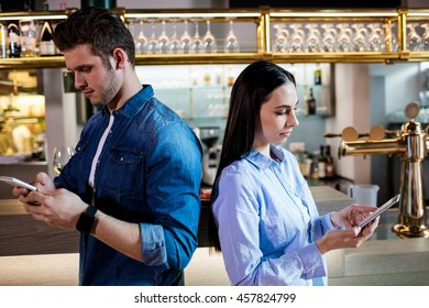 Side view of man and woman using mobile phone by bar counter