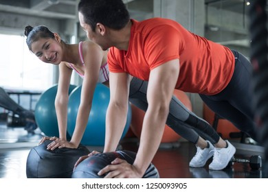 side view of man and young woman flirting and smiling each other while exercise in gym
