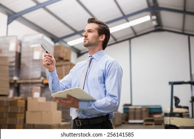 Side view of manager holding clipboard in the warehouse