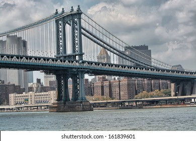 Side view of Manhattan Bridge structure and New York buildings.