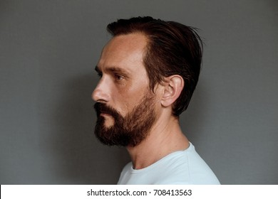 Side view of mans face on grey background. Mid aged actor posing for camera in studio.