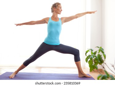 Side view of mature healthy sporty woman using a yoga mat to exercise and balance, stretching her body in a light and airy interior. Fit professional woman exercising and stretching her body, indoors.